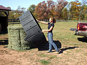 A woman loading the horse hay feeder in a pasture.
