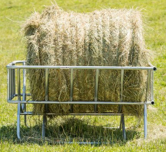 A cradle style bale feeder with a large round bale in pasture.