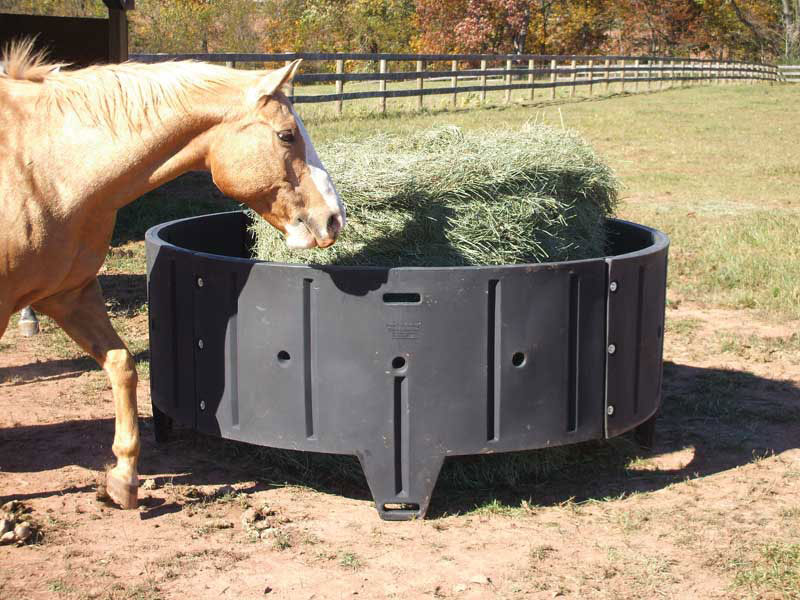 A poly round horse hay feeder with a round bale in it and a horse walking by.