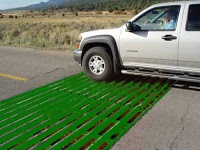 cattle guard installed in the road with a truck driving over it