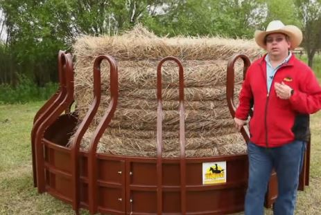 A big cattle and horse hay feeder with a cowboy next to it.