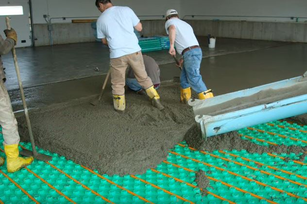 pouring cement over radiant floor heating panel insulation