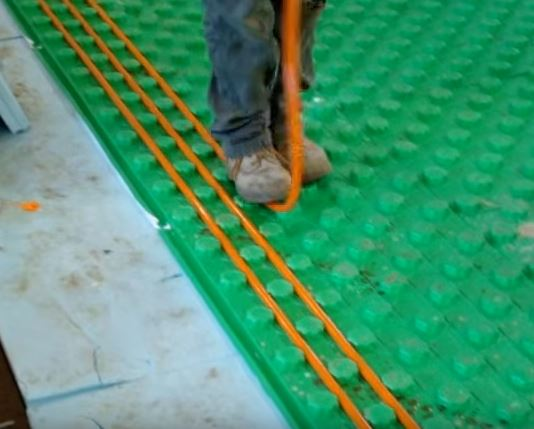 installing the pex tubing into the floor insulation panels