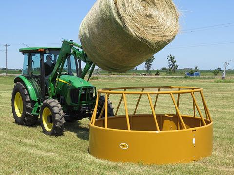 cattle hay feeder being loaded in the pasture