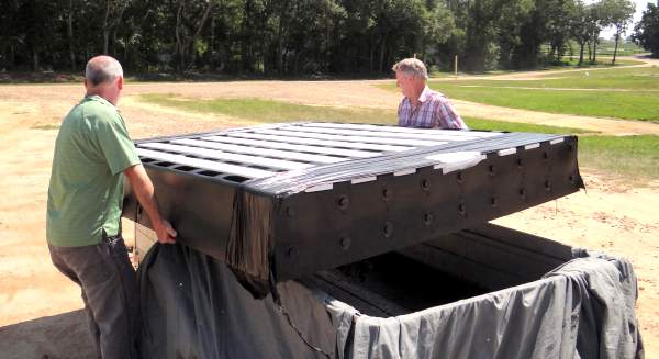 large concrete cattle guard form being unloaded by two people