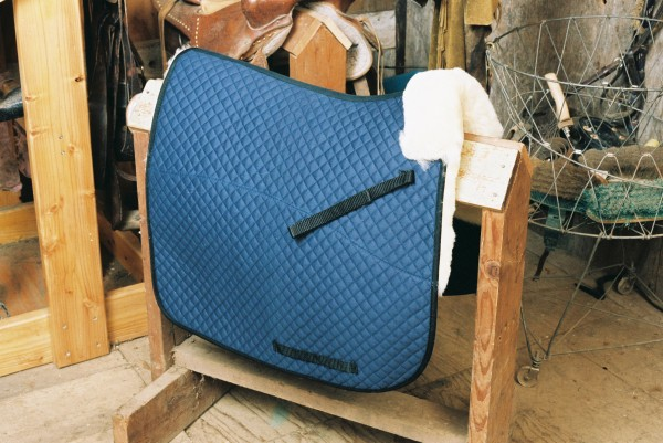 sheepskin saddle pad with blue quilting and pommel roll