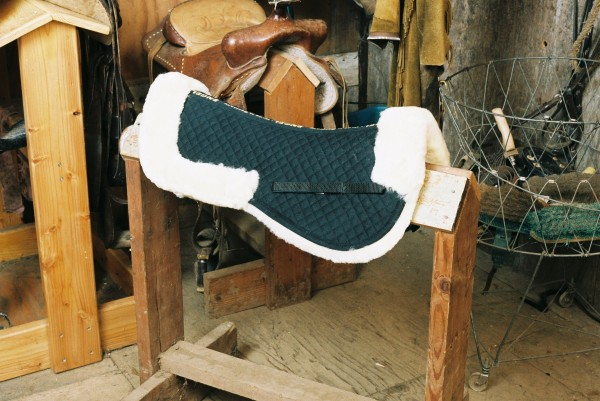 half sheepskin saddle pad with black quilting, pommel and cantle rolls