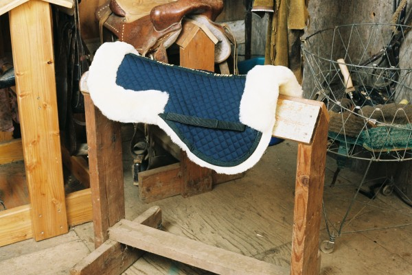 sheepskin half pad with blue quilting and pommel and cantle rolls