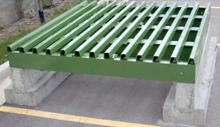 cattle guard resting on concrete foundations