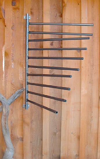 saddle pad rack mounted to the wall with 10 arms