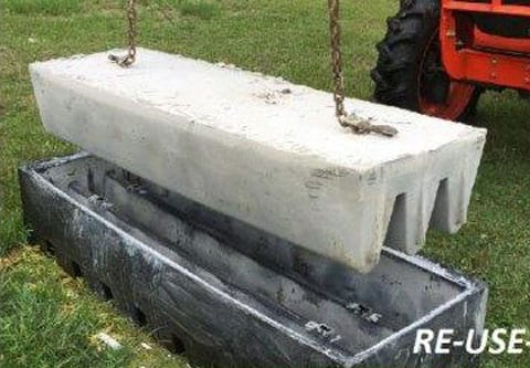 reusable concrete cattle guard form with tractor pulling out a finished guard